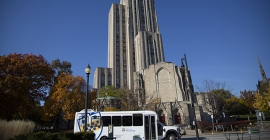 A campus shuttle with the cathedral of learning in the background.