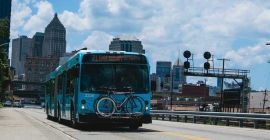 A blue port authority bus with bikes on the front.
