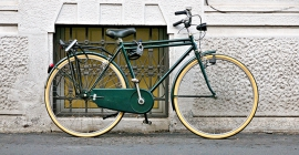 A green and yellow bike leaving against a wall.